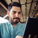 Menu digital dans la restauration. On voit un client qui regarde le menu sur une tablette.